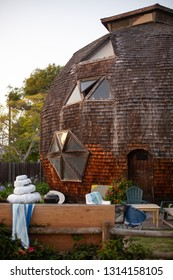 """Isla Vista, California / USA - April 20, 2014: Side of an iconic round Buckminster Fuller """"Buckyball"""" house, with geometric wood panels, in an architectural background"""