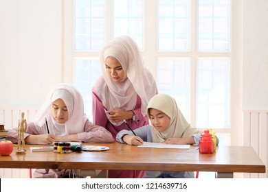 islam education concept, Adult muslim female teaching with art to learning a two child girl in home.