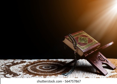 Islam holy book of Muslims, the Quran, is placed on a wooden stand, black background.
