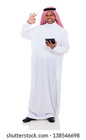 islam man giving okay hand sign and holding tablet computer on white background