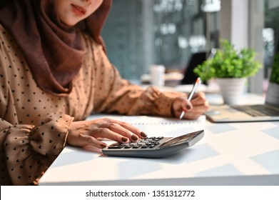 Islam woman working with finance calculate on calculator.