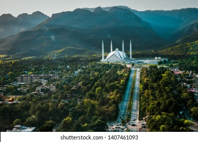 Islamabad / Pakistan - April 25 2019: Aerial photo of Islamabad, the capital city of Pakistan showing the landmark Shah Faisal Mosque and the lush green mountains of the city