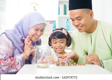 Islamic banking concept. Southeast Asian family counting money at home. Little Malay girl and parents saving money. Muslim father, mother and daughter living lifestyle.