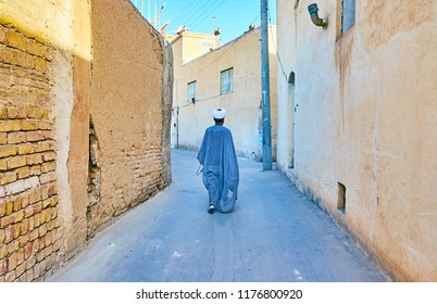 Islamic cleric (mullah) walks the old narrow curved street of the city with high wall-fences, Kashan, Iran.