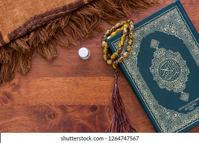 Islamic Concept. Flat lay composition with Muslim prayer beads, Quran, prayer rug, perfume bottle and space for text on wooden background. Quran is public item for all Muslims.