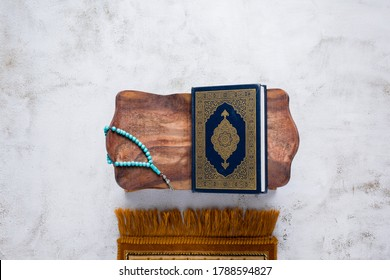 Islamic concept - The Holy Al Quran with written Arabic calligraphy meaning of Al Quran and rosary beads or tasbih and prayer rug, on wooden stand, with copy space.