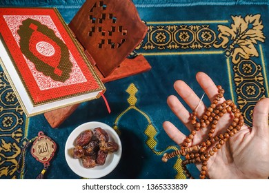 An islamic concept for Ramadhan. Flat lay composition of Qoran, Dates and a man's hand praying with tasbih (rosary beads) on his hand on top of a sajadah (praying mattress)