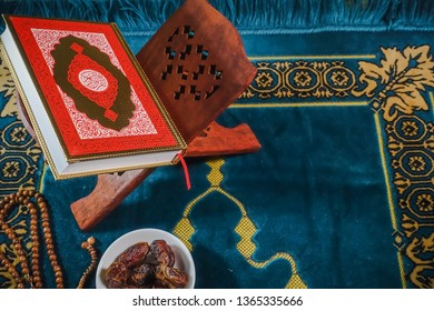 An islamic concept for Ramadhan. Flat lay composition of Qoran, Dates and a tasbih (rosary beads) on top of a sajadah (praying mattress)