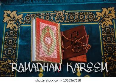 "An islamic concept for Ramadhan. Flat lay composition of Qoran, Dates and a tasbih (rosary beads) on top of a sajadah (praying mattress) with ""RAMADHAN KAREEM' wording"