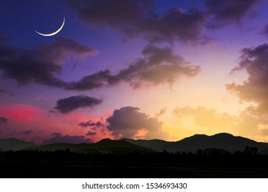Islamic Crescent Moon on Dark Blue Dusk sky,Twilight Sky in the Evening with Sunset and Beautiful Sunlight on dark cloud over silhouette mountain.