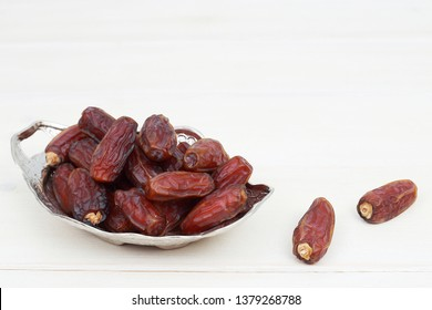 Islamic festival of Ramadan concept. with a delicious tropical dates on a silver plate and shiny rosary on a white wooden table background. Traditional Middle East culture. Ramadan Kareem.