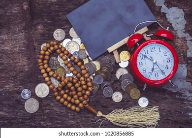 Islamic finance conceptual, rosary ,black board , red clock and coins.copy space area.