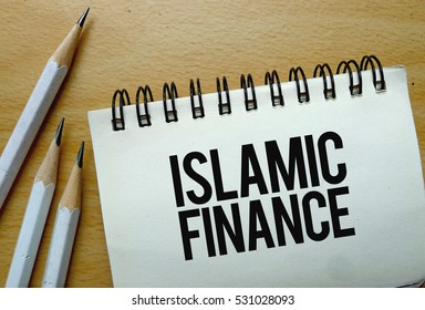 Islamic Finance text written on a notebook with pencils