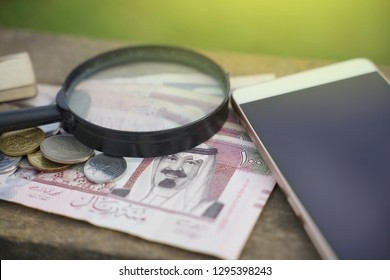 Islamic finance,magnifying glass and banknote Saudi Arabia with mobile phone.