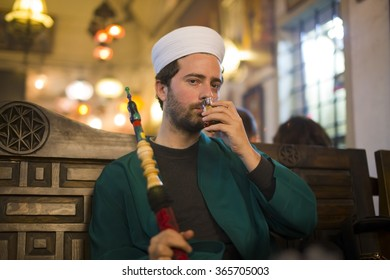 islamic man with traditional dress smoking shisha, drinking tea