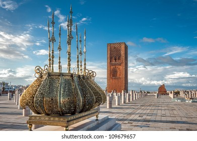 Islamic muslim religious architecture. Traditional golden decorations with the emblem of Morocco. Tour Hassan tower in a background with stone columns, Rabat Morocco.