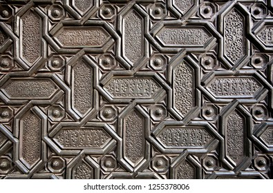 Islamic patterns and Arabic calligraphy in metal surface of door the 16th centure Seville Cathedral, Spain. Motifs in artworks of Andalusia.