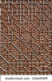 Islamic Persian design consisting stars and flowers, carved on the surface of an old wooden door.