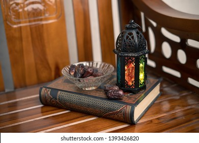 Islamic, ramadan and praying concept. Arabic lantern, dates or kurma with arabic book known as kitab or Quran on classic shine wood background, copy space, selective focus.