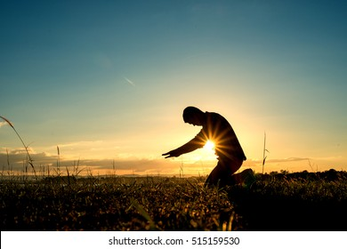 Islamic religion. Silhouette of man praying at the sunset on a background blue sky