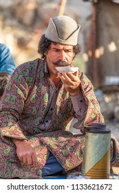 Islamic Republic of Iran.  Fars Province. Community of Qashqai nomads. Male traditional clothing and hat. Drinking tea.  March 10, 2018