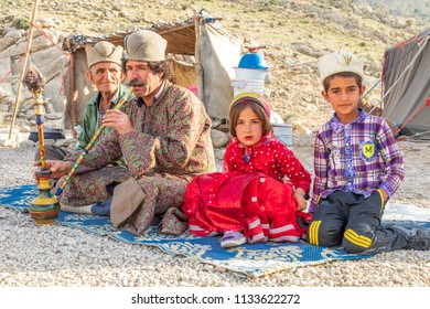 Islamic Republic of Iran. . Fars Province, Rudbal. Qashqai nomads, males are smoking a shisha, hooka, or water tabacco pipe. Young children in traditional clothing.  March 10, 2018