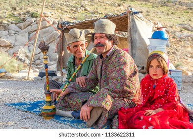 Islamic Republic of Iran. . Fars Province, Rudbal. Qashqai nomads, males are smoking a shisha, hooka, or water tabacco pipe. Young girl in traditional clothing.  March 10, 2018