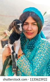 Islamic Republic of Iran. . Fars Province, Rudbal. Qashqai nomads, female with baby goat. Traditional clothing.  March 10, 2018