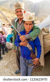 Islamic Republic of Iran. . Fars Province, Rudbal. Qashqai nomad boy and adult male,  holding hunting rifle.  March 10, 2018