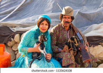 Islamic Republic of Iran. . Fars Province, Rudbal. Qashqai nomads, Husband and wife traditional clothing. Holding goats.  March 10, 2018