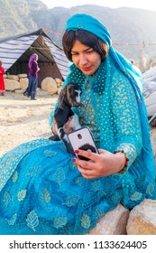 Islamic Republic of Iran. . Fars Province, Rudbal. Qashqai nomads, female with baby goat. Traditional clothing. Taking her photo with cell phone.  March 10, 2018