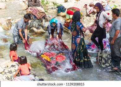 Islamic Republic of Iran. . Fars Province, Rudbal. A small community of Qashqai nomads, washing clothes in river stream.  March 10, 2018