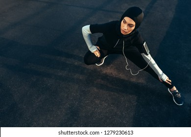 Islamic woman stretching after workout outdoors in the street. Muslim woman in sportswear exercising in morning.
