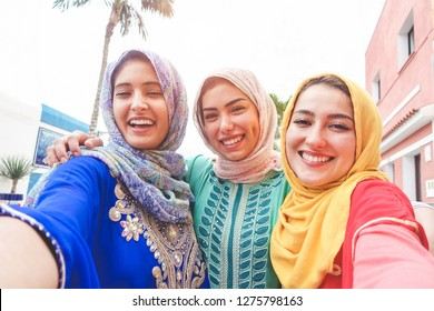 Islamic young friends taking selfie with smartphone camera outdoor - Happy arabian girls having fun with new trend technology - Friendship and millennial app concept - Focus on faces