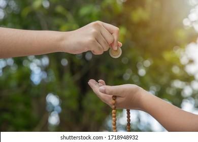 Islamischer Zakat oder Sadaka, Erwachsener, der Kind Geld spendet. Nahaufnahme einer Hand, die Münze auf Bokeh-grünem Hintergrund.