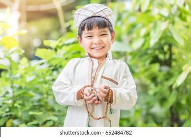 Islamischer Zakat oder Sadaka, Erwachsener, der Kind Geld spendet.Boy asian.Spende an Wohltätigkeitsorganisation für Kinder.