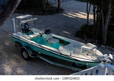 Islamorada, Florida USA 11-26-2018 Skiff in the Florida Keys on a gravel driveway late in the day after fishing with dramatic lighting close to sunset.