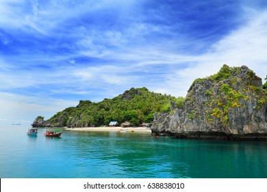 An island with the big rock with clear and smooth emerald green sea water, white cloud and blue sky. Three boats are near the beach, cottages are on the beach, tourists are snorkeling near the rock