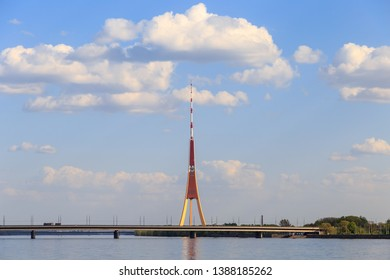Island bridge (Salu tilts) over Daugava river and radio and TV tower (Rigas radio un televizijas tornis) in Riga, capital of Latvia, on a sunny day under beautiful clouds in a blue sky.