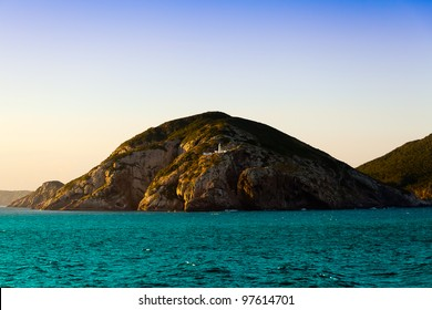 Island of Cabo Frio in the state of Rio De Janeiro, Brazil. View from a cruise ship cruising through Atlantic Ocean. In the center of the island there is a lighthouse and the moon is on the sky.
