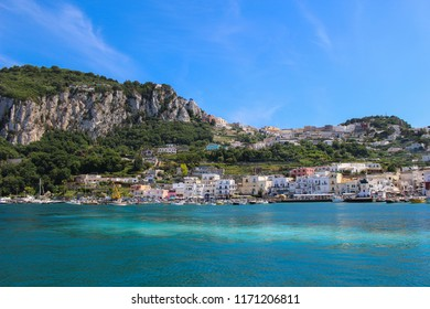 The island of Capri with boats and houses along the shore with blue sky and clear blue water in Italy