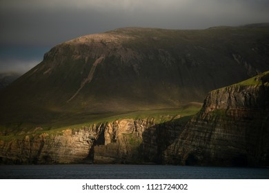 Island cliffs lighted up with setting sun in the evening during stormy weather on Orkney island, Scotland