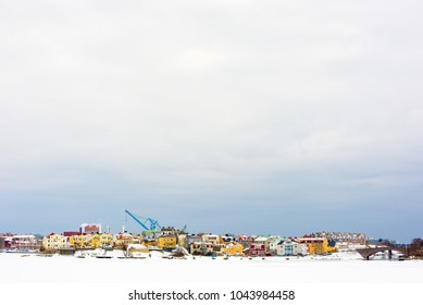 The island Ekholmen in Karlskrona, Sweden, with the city wharf and cranes in the background. Winter view with frozen sea and snow. Copyspace in sky above.