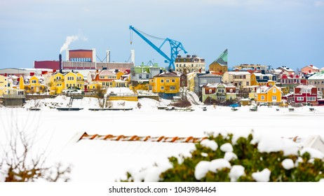 The island Ekholmen in Karlskrona, Sweden, with the city wharf and cranes in the background. Winter view with frozen sea and snow.