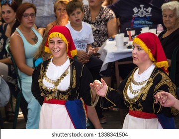 Island of Evia, Greece. August 2018: Greek beautiful girls in national costumes dancing traditional Greek dance at the festival in front of the audience