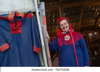 Magerøya Island, Finnmark , Norway, - September 1 2016 : an old sami woman dressed in her traditional clothes standing next to door of her hut