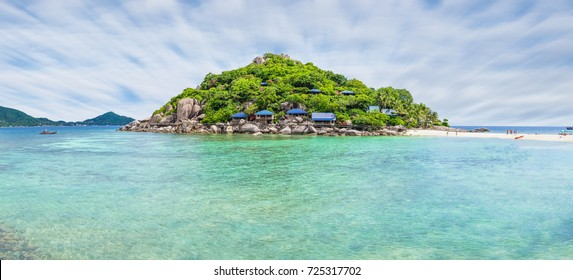 the island at koh tao surattani thailand, there are many tree stone and resident resort on island with moving cloud above sky and clear water of the sea