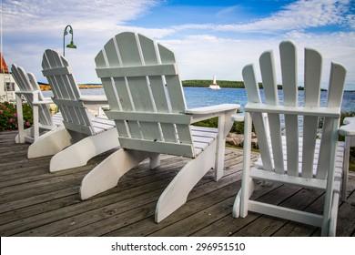 Island Life. Adirondack chairs line a wooden deck overlooking the Mackinaw Island waterfront with a lighthouse in the background. Mackinaw Island, Michigan.
