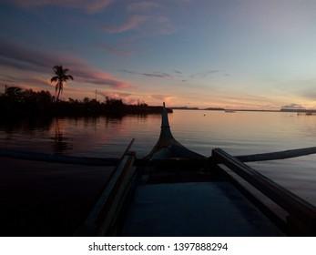Island Living: rosy dawn reflected in calm sea