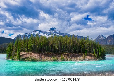 Island in the middle of a blue, green river. Beautiful colors. the clouds and mountains makes a wonderful canvas.